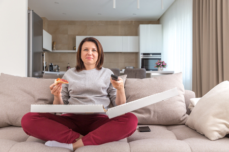 Girl eating pizza sitting on couch and watching tv in modern appartment Banco de Imagens - 121419763