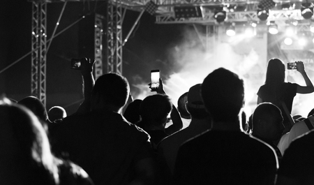 Black and White Silhouette of People in Crowd at a Music Festival. Concert with backlit standing dancing people