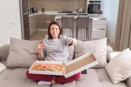 Meisje eet pizza zittend op de bank en tv kijkend in modern appartement