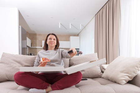 Girl eating pizza sitting on couch and watching tv in modern appartment