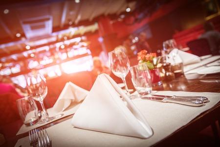 Bella tavola apparecchiata con bagliore di luce rossa
