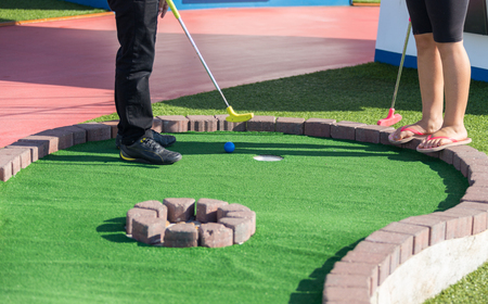 A man prepares to hit a ball during mini golf game Banco de Imagens