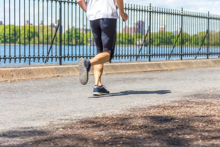 Athletic man running along lak in the nature. Healthy lifestyle