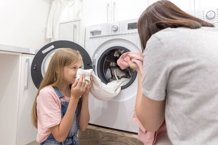 Happy family mother housewife and child daughter in laundry with washing machine and clothes