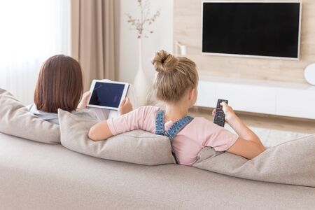 Mother and daughter sitting on couch watching tv in living room Stockfoto