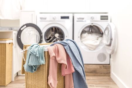 Laundry basket with dirty clothes with washing and drying machines on the background 写真素材
