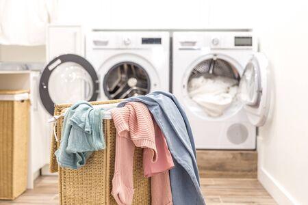 Cesto della biancheria con vestiti sporchi con lavatrici e asciugatrici sullo sfondo