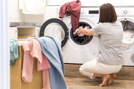 Young Woman loading washing machine and a Basket Full Of Dirty Clothes In Laundry Room 免版税图像