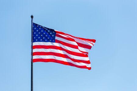 American flag on the blue sky on the wnd 免版税图像
