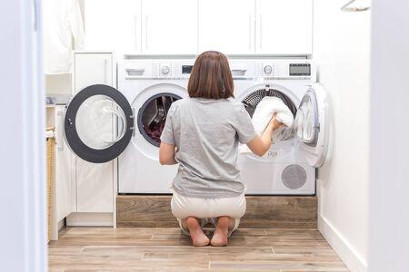 Woman putting clothes to washing machine for wash Banco de Imagens