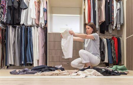 Mujer joven tirando ropa en el vestidor. Lío en armario y vestidor Foto de archivo