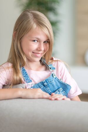Portrait of blonde pre-Teenage Girl sitting on couch