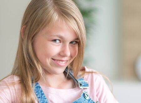 Portrait of blonde pre-Teenage Girl sitting on couch Stock Photo
