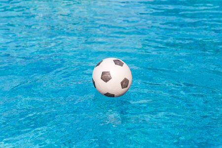Soccer ball floating in the swimming pool