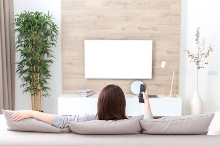 Young woman watching TV in the room. white empty screen for design Imagens