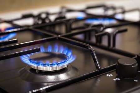 Blue flames on gas stove burner at home