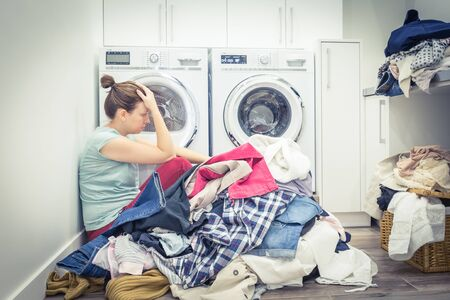 Unhappy Stressed Woman with Pile Of Clothes Near Washing Machine in laundry room, blue tone Foto de archivo