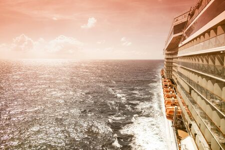 Side view of cruise ship on the blue sky background with copy space, orange tone