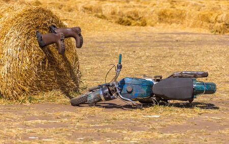 A motorycle near the haystack and boots in the pile of straw. crash humor concept decoration