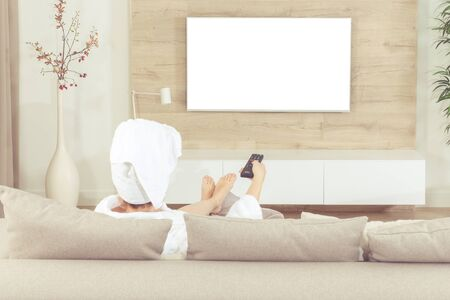 Woman sitting on couch with towel on her head after shower watching tv. White screen cut out for design Banco de Imagens