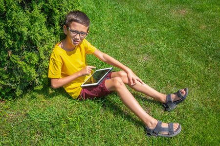 Cute boy playing internet games with tablet on a sunny day Stockfoto