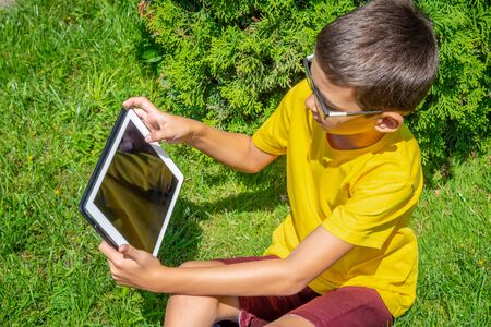Boy holding tablet PC on green grass lawn Stockfoto - 128616653