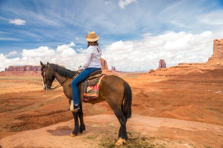Cowgirl riding horse in Monument Valley Navajo Tribal Park in USA