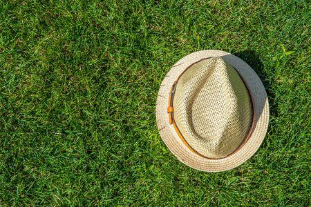 Straw hat on the green grass background Foto de archivo