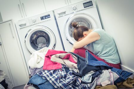 Sad tired Woman in laundry room, blue tone Banco de Imagens