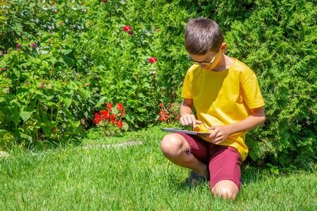 Boy sitting on the lawn in a park with tablet reading electronic book Banco de Imagens