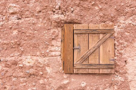 Old small closed wooden window on a stone wall with copy space
