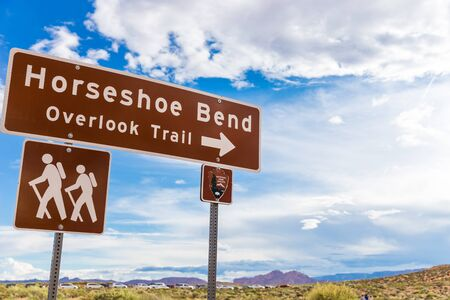 Horseshoe Bend sign pointing to overlook trail with blue sky