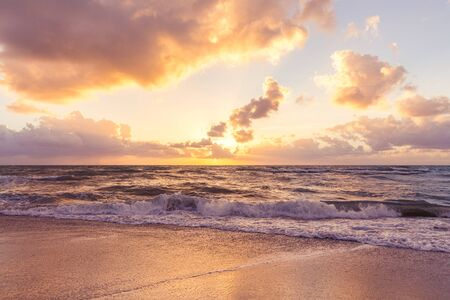 Beautiful cloud coastline background. Fiery orange sunset sky. Amazing sunrise on the beach in Miami. Orange tone