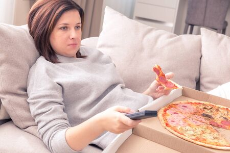 Surprised woman eating pizza and watching TV with remote control at home, warm tone Stock Photo