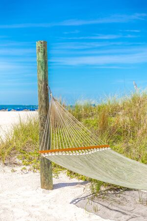 Summer beach relax with empty hammock and ocean background on tropical beach, vacation concept