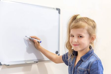 Little girl smiling and pointing to empty whiteboard with a marker pen. Learning concept with copy space Banco de Imagens