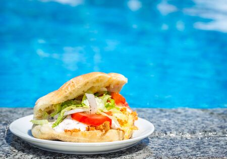 Fresh Sandwich on a plate near the swimming pool