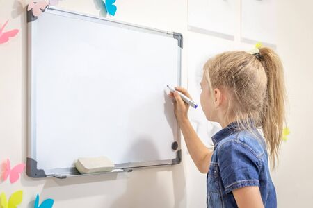 Little girl writing on empty whiteboard with a marker pen. Learning, education and back to school concept with copy space Banco de Imagens