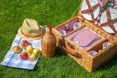 Picnic basket on green sunny lawn in the park Banco de Imagens