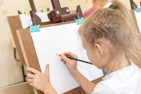 Little girl drawing a picture on easel in classroom