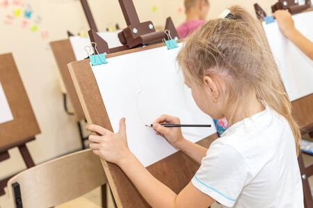 Kid drawing image on easel in classroom Banco de Imagens