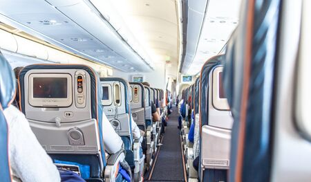 Interno dell'aereo con passeggeri sui sedili in attesa di decollare