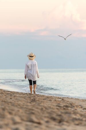Woman wearing white shirt and straw hat walking on beach at sunset