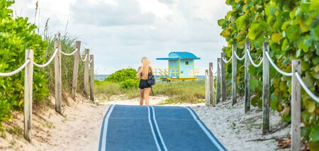 Girl walking to the beach on Footpath. South Beach in Miami, Florida, USA