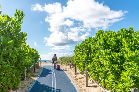 Girl with suitcase walking to the beach on Footpath. South Beach in Miami, Florida, USA