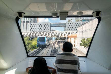 MIAMI - September 10, 2019: The fully automated Miami downtown train system with the city in the background. Father and son, view from inside of train