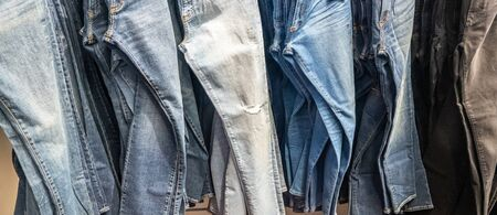 Jeans hanging on a rack. Row of denim pants. concept of buy, sell , shopping and jeans fashion Banco de Imagens