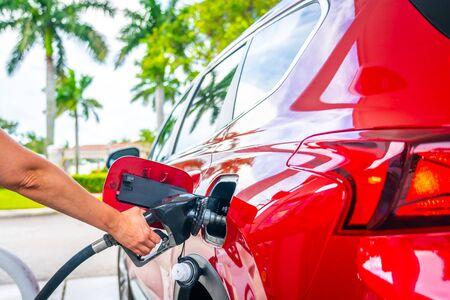 Main féminine avec pistolet à essence et voiture rouge