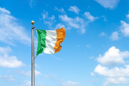 Irish tricolour flying in full sunshine against blue sky