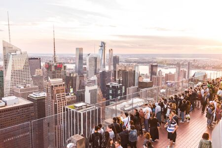 NEW YORK, USA - 17 MAY, 2019: Tourists taking pictures from rooftop on Manhattan skyscraper